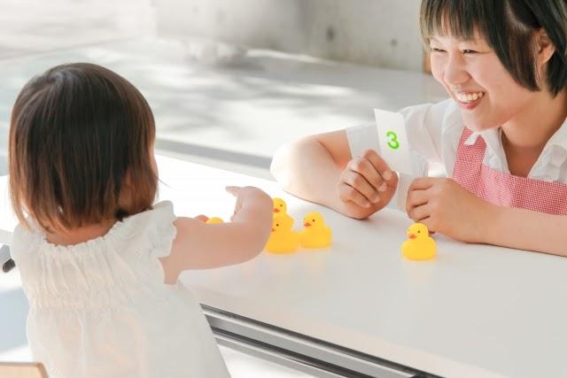 女児と遊ぶ保育士