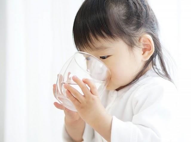 コップを持って水を飲む女の子