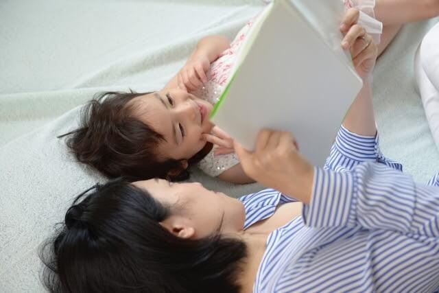 親子の読み聞かせの様子(寝転がりながら)