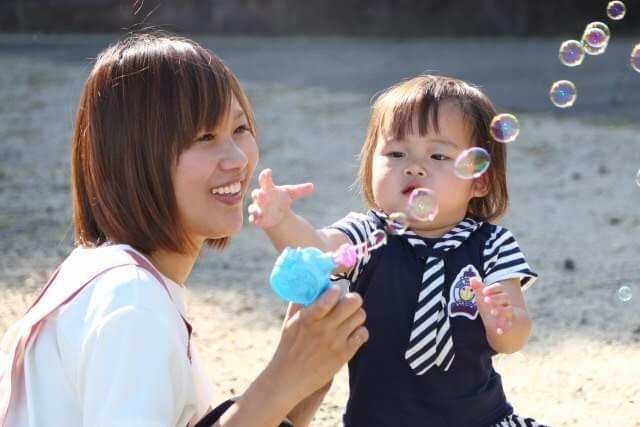 シャボン玉で遊ぶ幼児と幼稚園教諭実習生