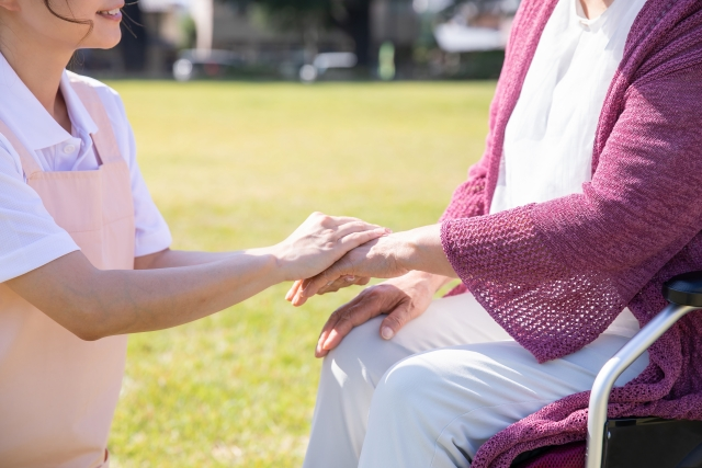 手を重ねるおばあちゃと介護士