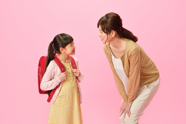 ランドセルを背負った小学生の女の子と母親