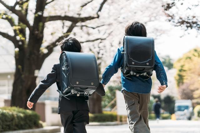 手をつないで登校するランドセルを背負った小学生