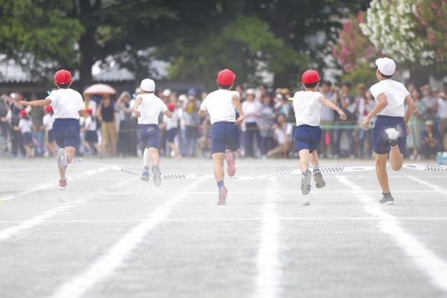 運動会で走る赤白帽の小学生