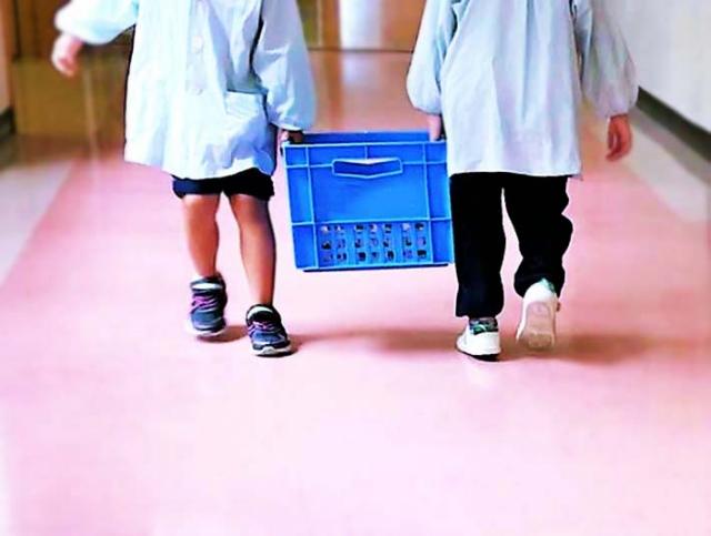 給食の牛乳を運ぶ子どもたち