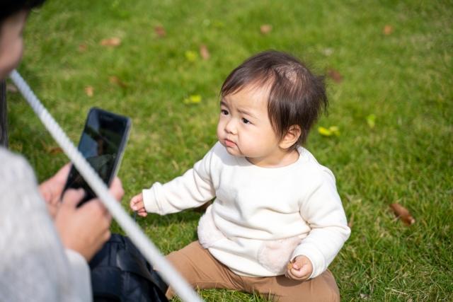 公園で赤ちゃんを撮影するママ
